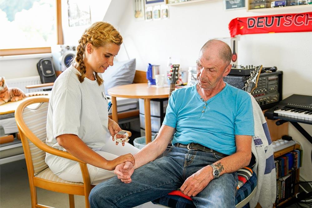 Pflegerin der alwo Unternehmensgruppe während des Puls messens eines Bewohners.